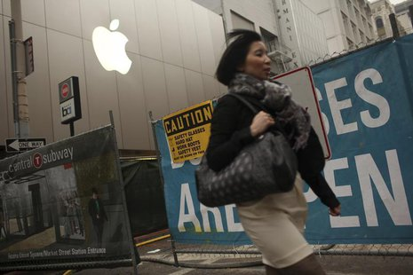 A woman walks past an Apple logo at the company's flagship retail store near signs for the central subway project in San Francisco, Californ