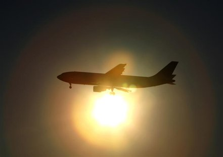 A Japan Airlines (JAL) aircraft is silhouetted against the setting sun as it prepares to land at Haneda airport in Tokyo January 17, 2010. R