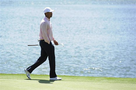 Tiger Woods of the U.S. walks along the 12th green during the 2013 Tavistock Cup golf tournament at Isleworth Golf and Country Club in Winde