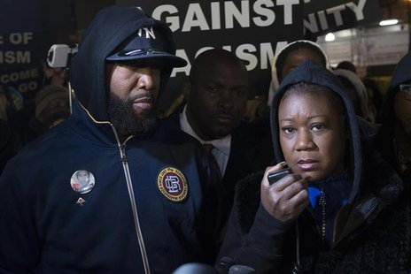 Tracy Martin (L) and Sybrina Fulton, the parents of Trayvon Martin, participate in a candlelight vigil to mark the anniversary of the shooti