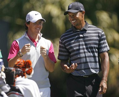 Rory McIlroy (L), of Northern Ireland shares a laugh with his playing partner Tiger Woods on the 12th tee during first round play in the 201