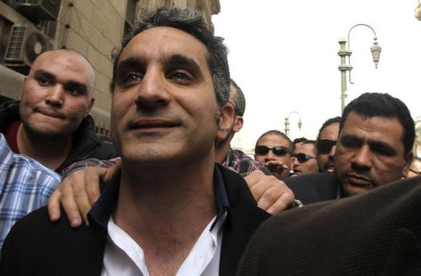 Bassem Youssef (C), the country's best-known satirist, gestures to journalists and activists as he arrives at the high court to appear at th