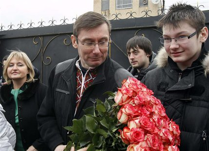 Ukraine's former interior minister Yuri Lutsenko (2nd L) receives flowers after leaving a prison in the settlement of Makoshino, with his wi