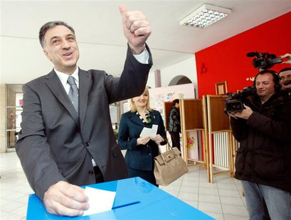 Montenegrin President Filip Vujanovic (L), accompanied with his wife Svetlana, gestures as he casts his vote during Montenegro's presidental