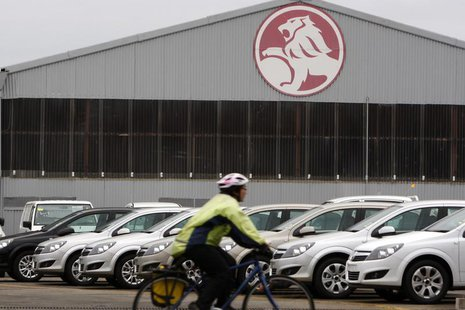 A cyclist rides past a General Motors (GM) Holden storage facility in Melbourne June 2, 2009. REUTERS/Mick Tsikas (AUSTRALIA TRANSPORT BUSIN