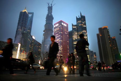 People walk along a busy street at Pudong financial district in Shanghai, March 27, 2013. REUTERS/Carlos Barria
