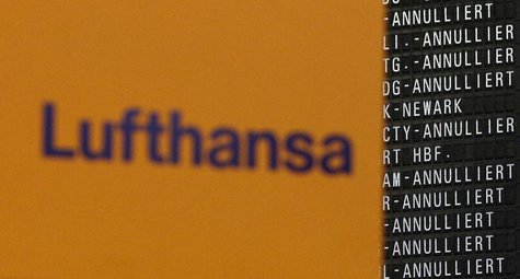 The Logo of German air carrier Lufthansa is pictured next to a departure board during a five-hour warning strike, following a pay dispute, r