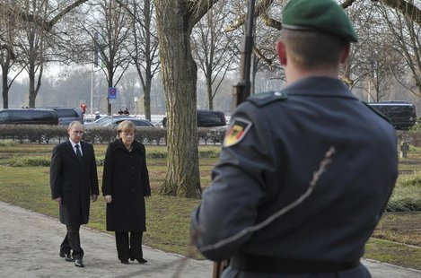 German Chancellor Angela Merkel and Russian President Vladimir Putin lay a wreath at the Cemetery of Honour on the north bank of the Maschse