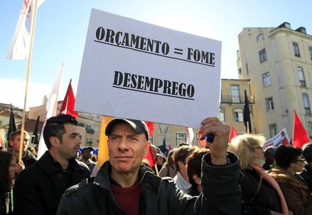 "A man holds a sign reading: ""Budget = hunger, unemployment"" during an anti-austerity protest in front of Portugal's parliament in Lisbon Nov"