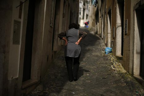 A woman walks at Alfama neighbourhood in Lisbon April 8, 2013. REUTERS/Rafael Marchante