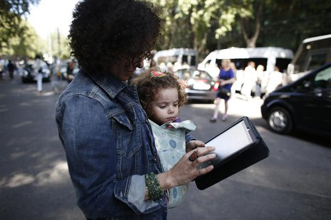 A woman carrying a child looks at an iPad tablet after the Emporio Armani Spring/Summer 2013 collection at Milan Fashion Week September 20,
