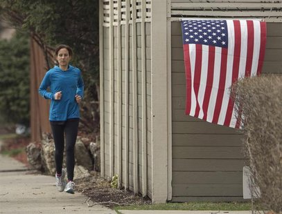 A jogger runs past a U.S. flag near the home of diplomat Anne Smedinghoff, 25, in River Forest, Illinois, April 8, 2013. REUTERS/John Gress