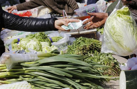 A woman pays for vegetables at a morning market in Beijing April 8, 2013. REUTERS/Kim Kyung-Hoon