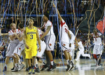 The Louisville Cardinals celebrate as Michigan Wolverines guard Trey Burke (3) leaves the court after Louisville won the NCAA men's Final Fo