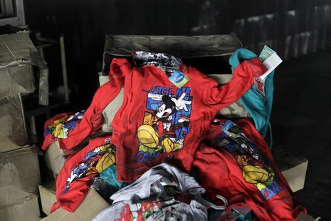 Clothes printed with Disney characters are seen among debris in the Tazreen Fashions garment factory, where 112 workers died in a devastatin