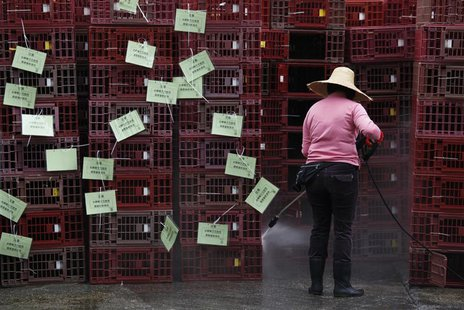 A worker cleans empty cages, which were used to transport chickens, after morning trading at a wholesale poultry market in Hong Kong April 8