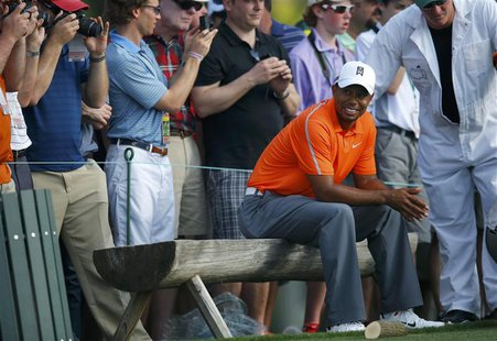 Tiger Woods of the U.S. sits after hitting his tee shot on the 18th hole during a practice round in preparation for the 2013 Masters golf to