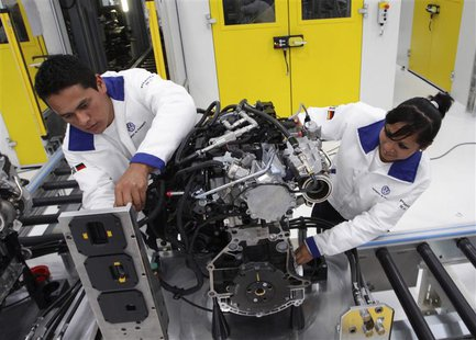 Technicians work on an engine during a media tour at the inauguration of Volkswagen's 100th plant worldwide in Silao in this January 15, 201