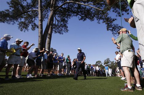 Phil Mickelson of the U.S. is applauded as he walks to the eighth tee during a practice round in preparation for the 2013 Masters golf tourn