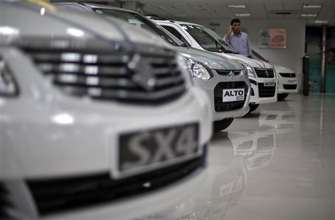 A sales executive speaks on his mobile phone as he stands in between Maruti Suzuki cars inside a showroom in New Delhi April 9, 2013. REUTER
