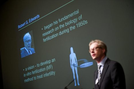 A picture of Robert Edwards of Britain is projected behind Christer Hoog of the Karolinska Institute as the winner of the 2010 Nobel Prize i