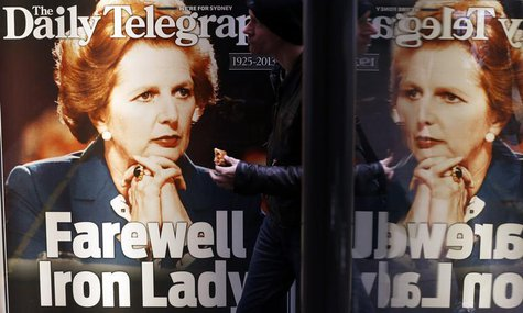 A man walks in front of a newspaper advertisement with the portrait of former British prime minister Margaret Thatcher in Sydney April 9, 20