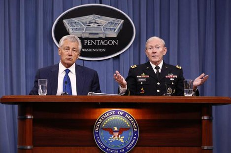 U.S. Defense Secretary Chuck Hagel (L) listens as Chairman of the Joint Chief of Staff General Martin Dempsey (R) speaks during a briefing o