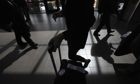 Passengers cast shadows as they walk along a terminal at Los Angeles International Airport in Los Angeles, California March 4, 2013. REUTERS