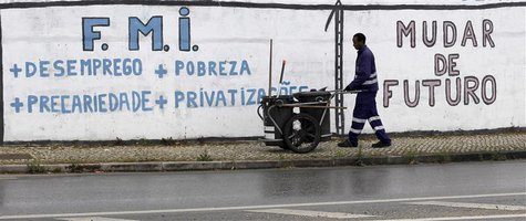 "A city cleaner works near a wall with graffiti that reads ""International Monetary Fund + Unemployment + Poverty + Precariousness + Privatiza"