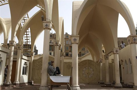 A Coptic Christian sits on a desk near the gate inside Cairo's main Coptic cathedral, following Sunday's clashes with Muslims, April 8, 2013