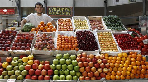 A fruit and vegetable trader stands at his stall in a market in St. Petersburg June 2, 2011. REUTERS/Alexander Demianchuk
