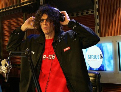 Howard Stern adjusts his headphones before the start of his news conference during the live debut broadcast of his show on Sirius Satellite