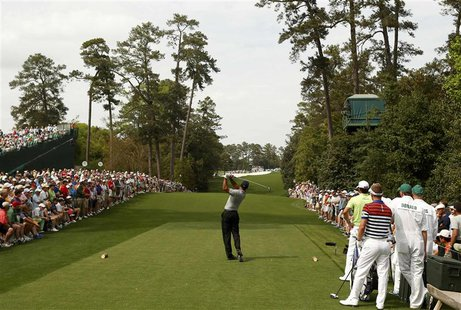 Tiger Woods of the U.S. hits his tee shot on the 18th hole during first round play in the 2013 Masters golf tournament at the Augusta Nation