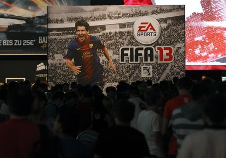 Visitors walk past an advertising placard of FIFA13 during the Gamescom 2012 fair in Cologne August 16, 2012. REUTERS/Ina Fassbender