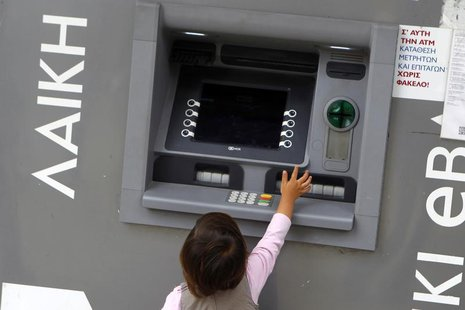 A child tries to reach an ATM machine at a branch of Laiki Bank in Nicosia March 30, 2013. REUTERS/Bogdan Cristel