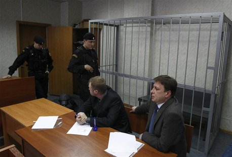 Attorneys of dead anti-corruption lawyer Sergei Magnitsky sit in front of an empty defendants cage during a court session in Moscow March 22