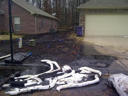 Spilt oil from Exxon pipeline runs between homes in North Woods Subdivision in Mayflower, Arkansas in this March 31, 2013 photo released to