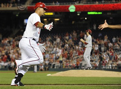 Washington Nationals' Wilson Ramos (L) reaches out to slap hands with coach Bo Porter (hand at R) as he rounds third base after hitting a ho