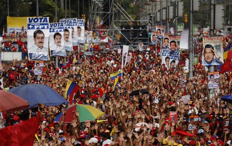 Supporters of Venezuela's acting President and presidential candidate Nicolas Maduro raise their hands during his closing campaign rally in