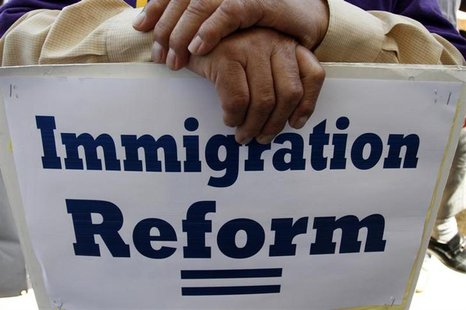 A man holds an immigration reform protest sign during a rally for immigration reform near Senator Dianne Feinstein's office, in Los Angeles,
