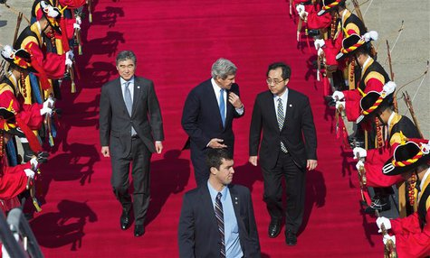 U.S. Secretary of State John Kerry (C) speaks with U.S. Ambasador to South Korea Sung Y. Kim (R) as they walk past a South Korean honor guar
