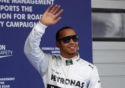 Mercedes Formula One driver Lewis Hamilton of Britain waves as he celebrates taking pole position after the qualifying session for the Chine
