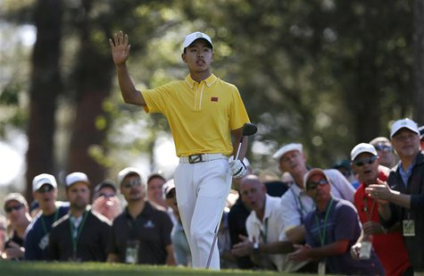 Amateur Guan Tianlang of China waves after hitting his tee shot on the fourth hole during third round play in the 2013 Masters golf tourname