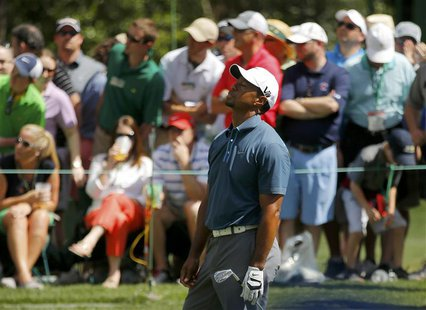 Tiger Woods of the U.S. reacts to his tee shot on the sixth hole during third round play in the 2013 Masters golf tournament at the Augusta