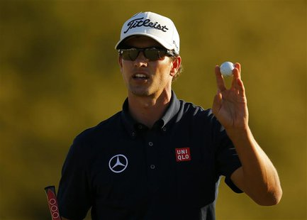 Adam Scott of Australia holds up his ball after sinking a par putt on the 18th green during third round play in the 2013 Masters golf tourna