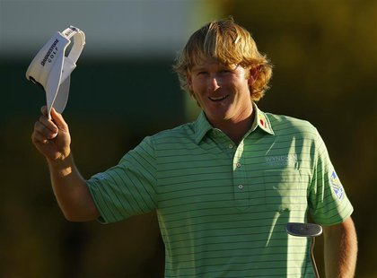 Brandt Snedeker of the U.S. waves after sinking a par putt on the 18th green during third round play in the 2013 Masters golf tournament at