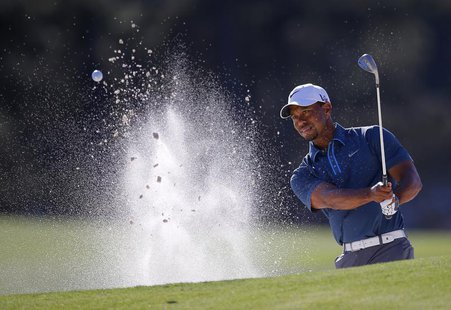 Tiger Woods of the U.S. hits from a sand trap on the 17th green during third round play in the 2013 Masters golf tournament at the Augusta N