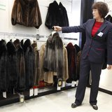 A sales woman displays a mink coat to customers at a shopping mall in Shanghai, April 4, 2013. Fueled by demand for high-end clothing and lu