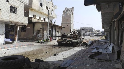 An abandoned tank is seen on a street near the minaret of the Omari mosque, which was damaged by what activists said was shelling by forces