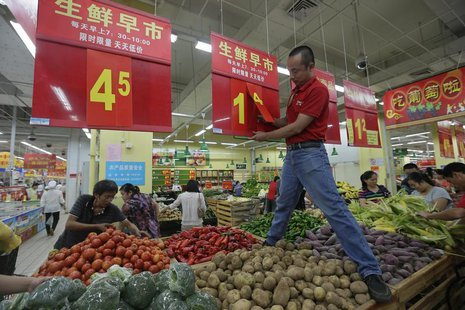 An employee adjusts a price tag at a supermarket in Wuhan, Hubei province, September 9, 2012. REUTERS/Stringer